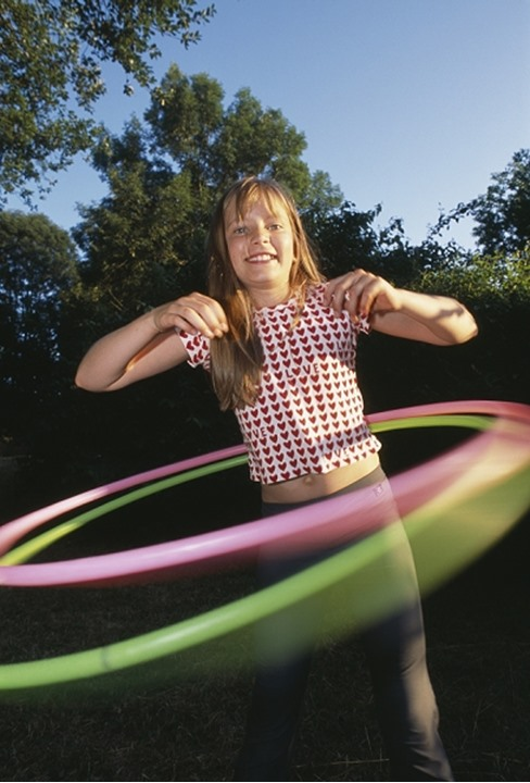 A girl playing with two hoola hoops at a time