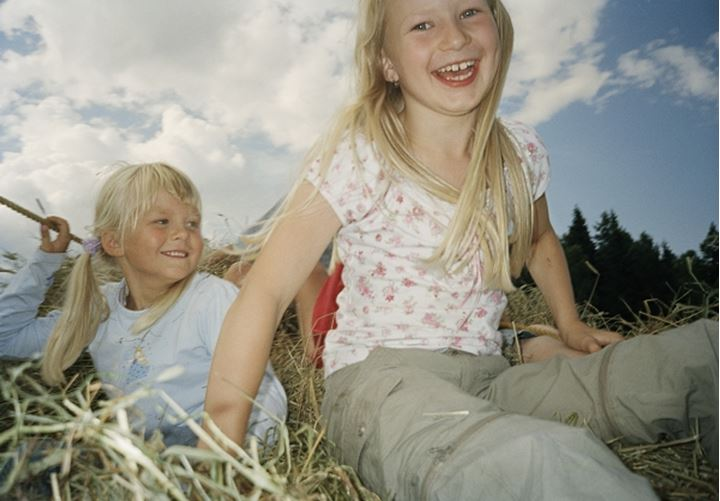 Two girls playing in hay-stack