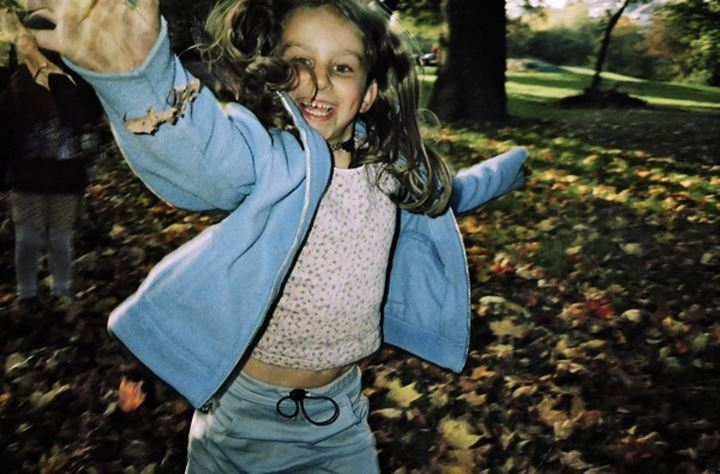 girl in park playing with leaves