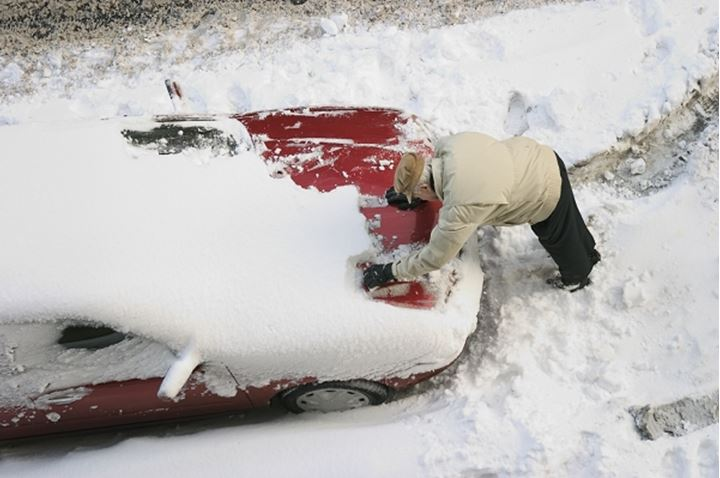 Man scraping off snow from car after a snow storm