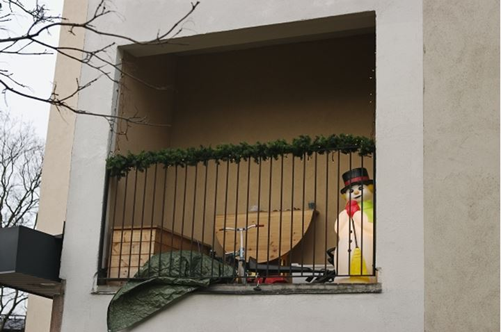 Covered balcony with snowman and bicycle