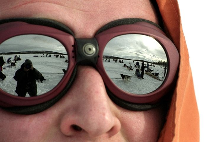 Reflection of dog sled in the sunglasses