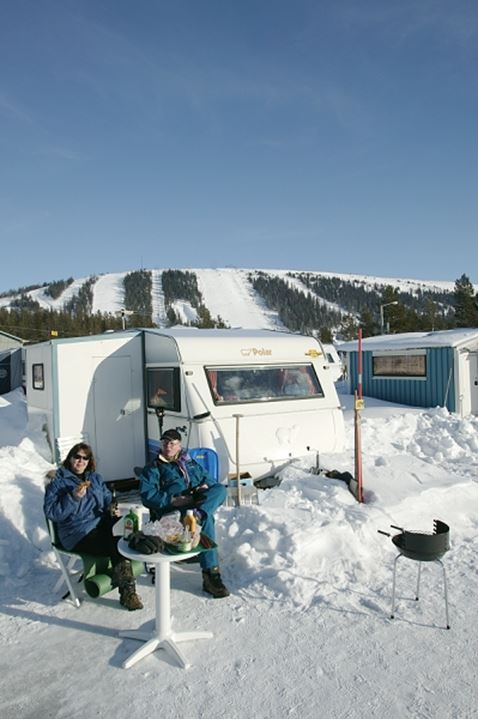 Couple sitting near a caravan in snow