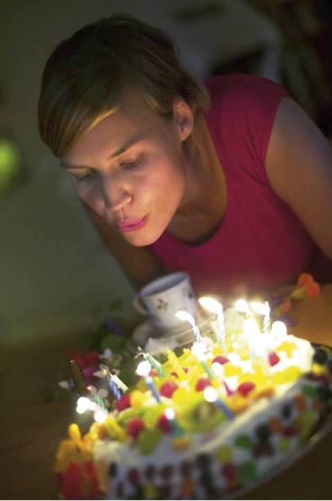 A woman blowing out candles on a birthdaycake