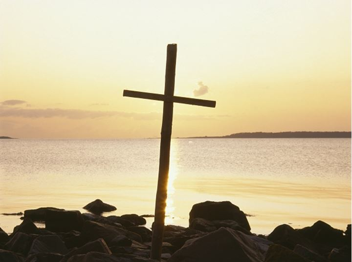 A big, wooden cross by the sea