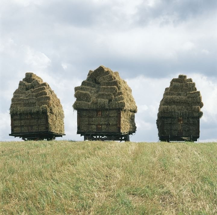 Three trailers stacked with hay bales