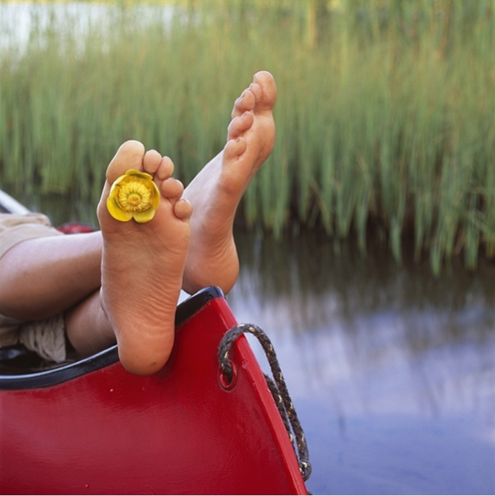 A barefeet person with a yellow flower between the toes, resting on a boat