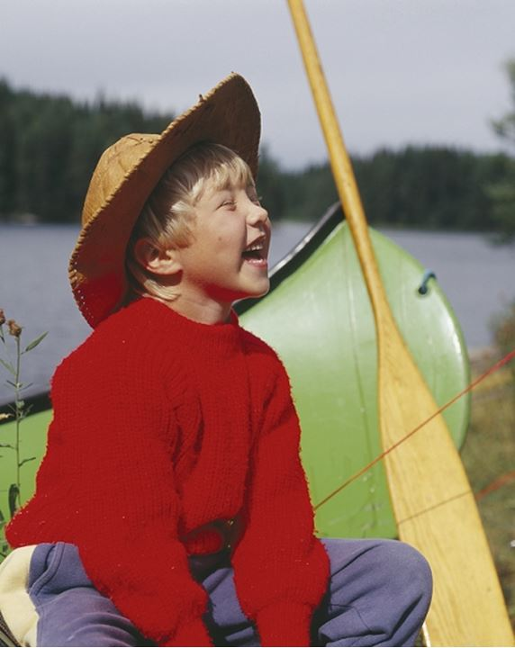 A laughing boy sitting by a canoe