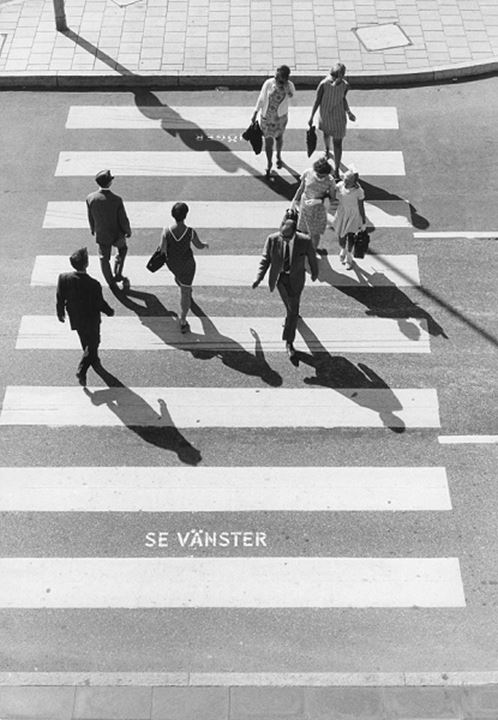 High angle view of people crossing road through the zebra crossing