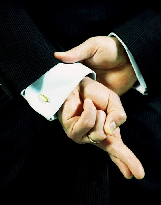 Close-up of a liar crossing his fingers behind his back