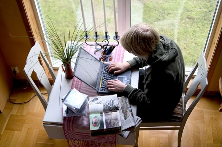 High angle view of a boy working on a laptop