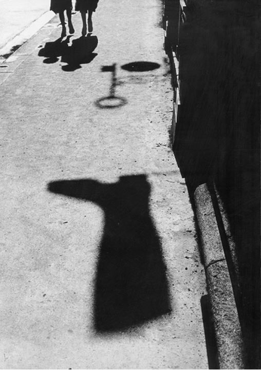 France, Paris - Low section view of two people walking in a street with objects casting shadow