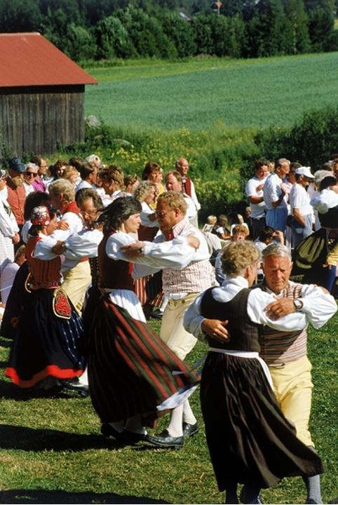 People wearing national costumes and dancing outdoors at Midsummer, Sweden