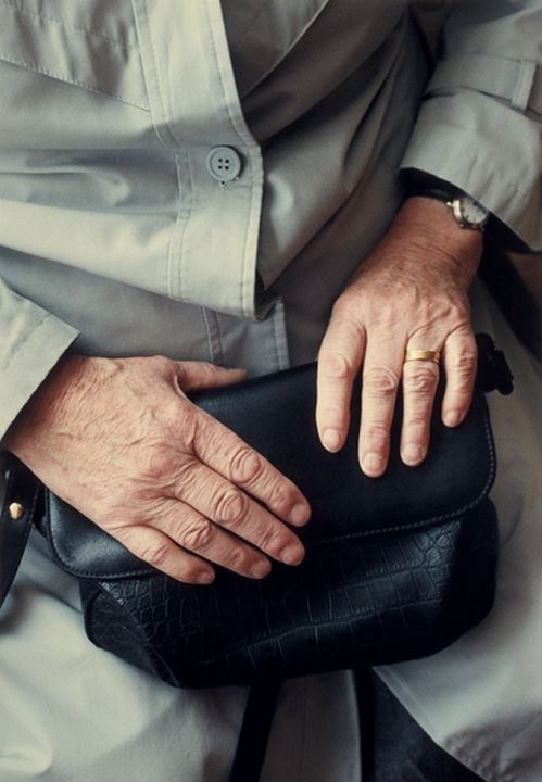 Mid section view of a senior man holding a hand bag