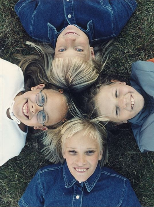 Smiling children lying on the grass
