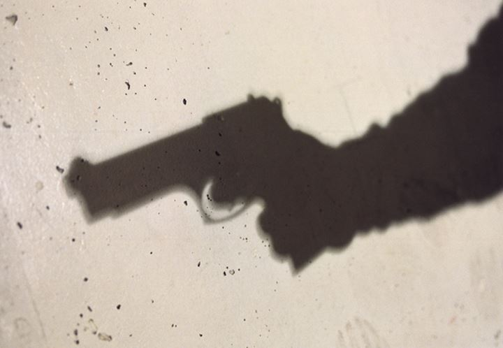 Shadow of a person's hand holding a hand gun on a wall