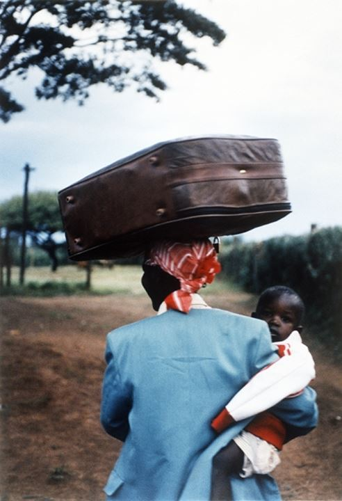 A woman carrying her baby and a bag on her head, Kenya