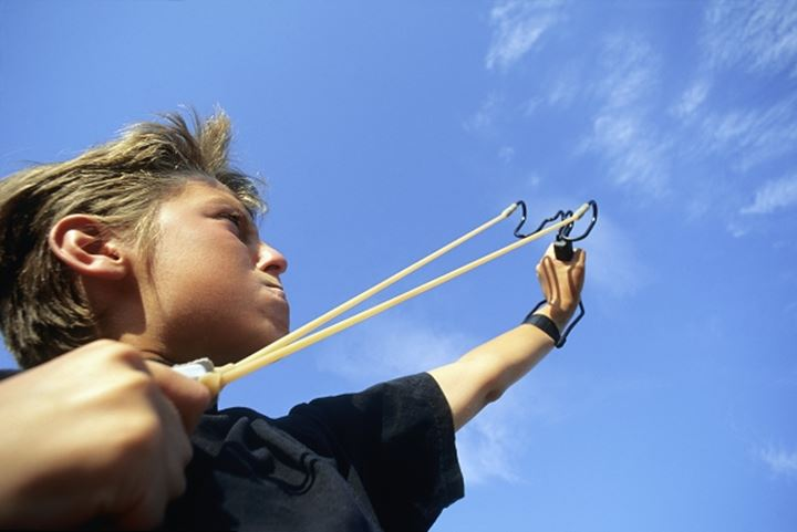A boy aiming a slingshot
