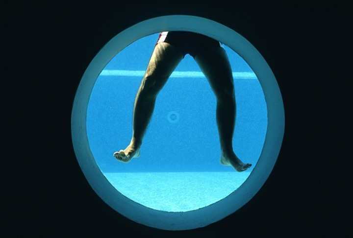 A man's legs seen underwater through a window at a swimming pool