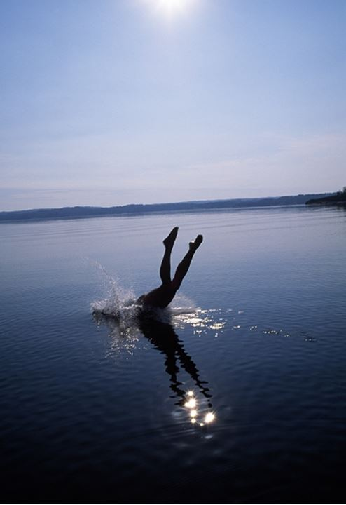 Legs of a person jumping into the water