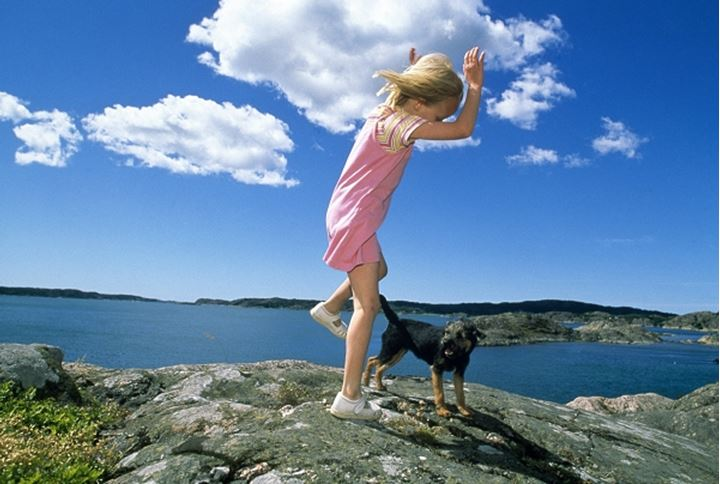 A girl playing with her dog near coast, Sweden