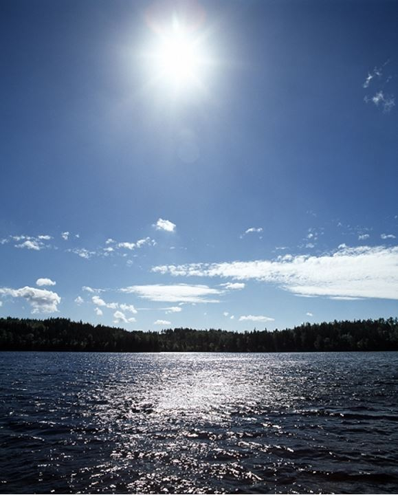 A lake illuminated by bright sunlight. Sweden