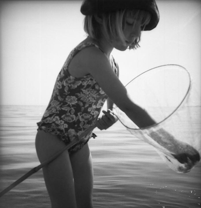 Girl in water with landing net, Sweden