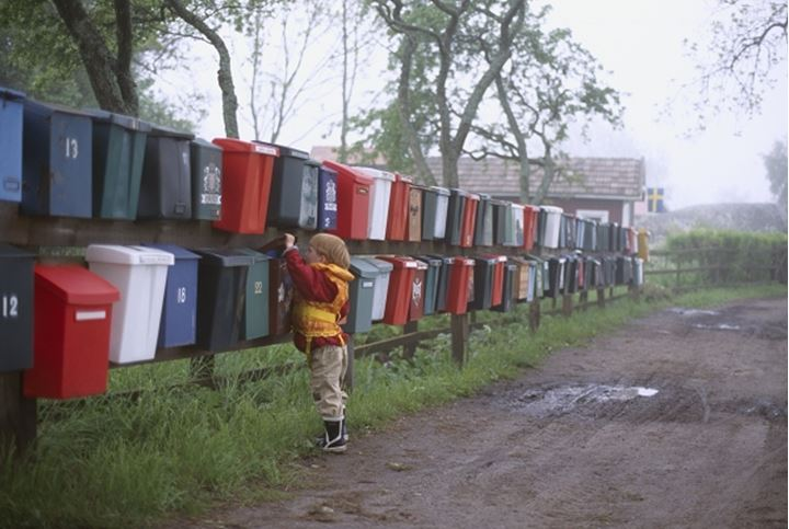A boy checking for mail in on of many mailboxes hanging on a fence