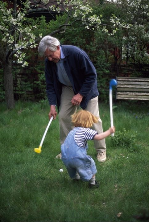 Senior man playing golf with his grandson in a garden