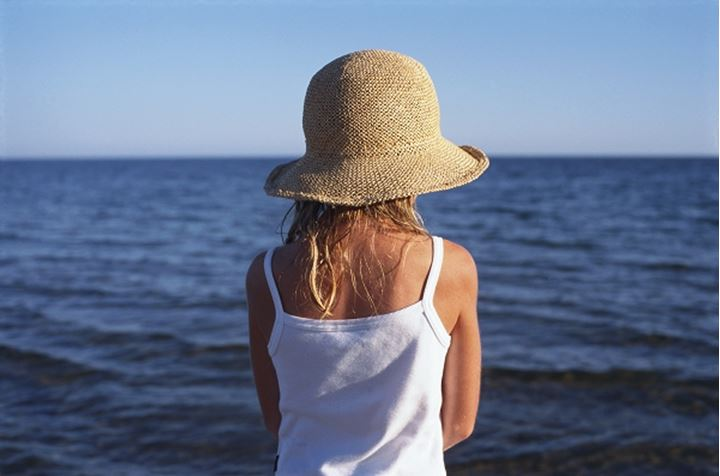 Back view of a girl towards ocean, Sweden