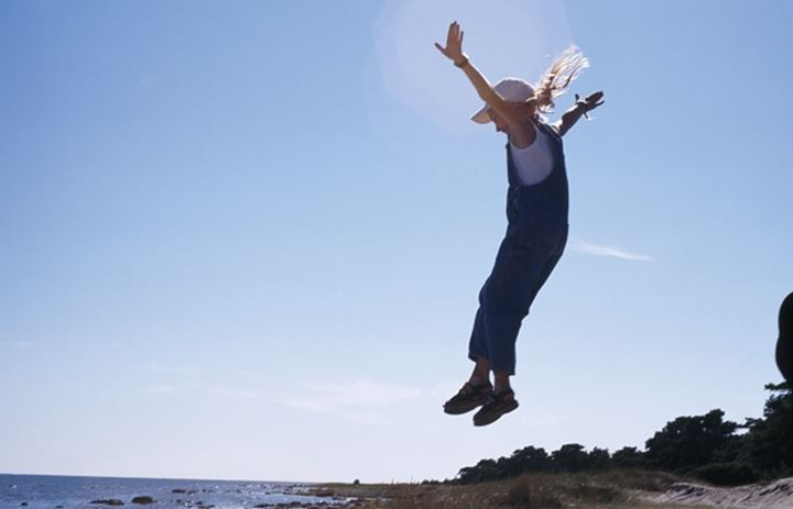 A girl jumping off a rock by the seaside