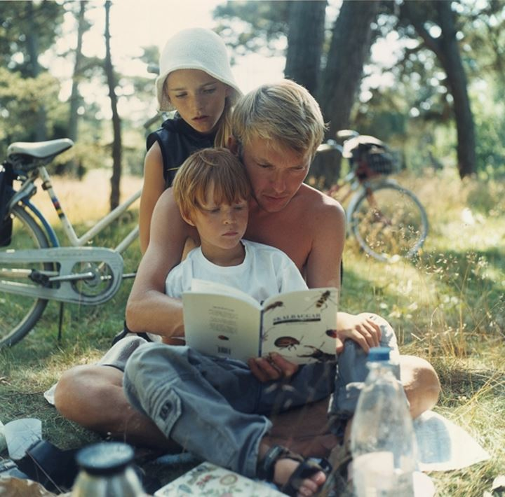 Father and sons reading outdoors. Sweden