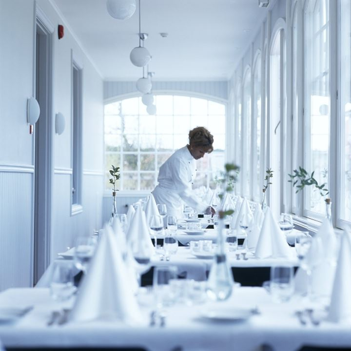 Side profile of a waitress setting tables in a restaurant