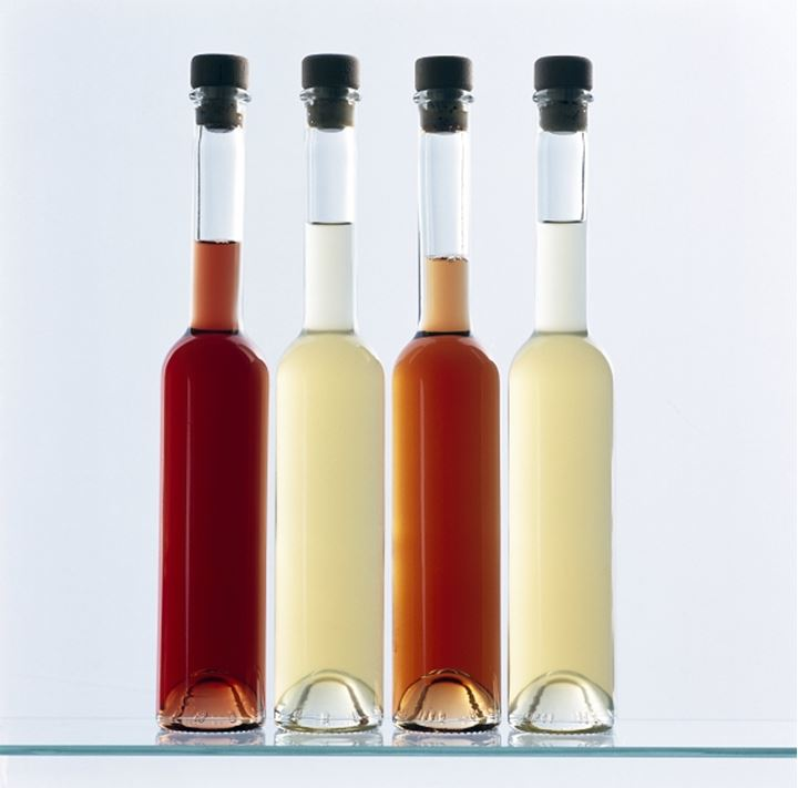 Close-up of four bottles of vinegar