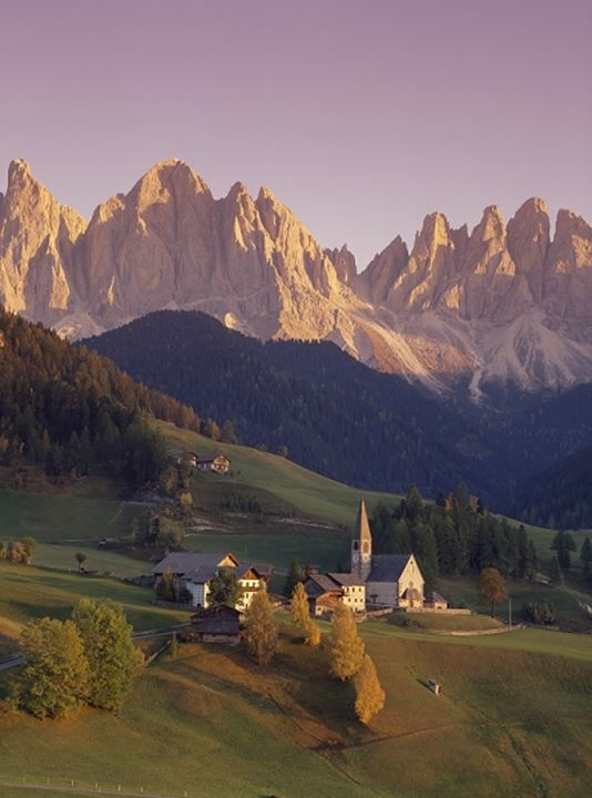 High angle view of a church on a landscape with mountains in the background, Italy