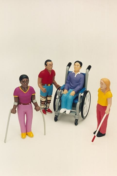 High angle view of figurines of four physically challenged people