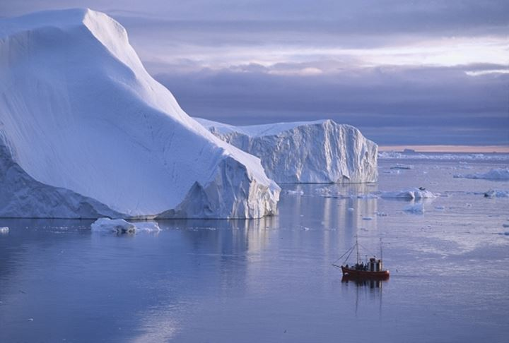 A boat sailing by a huge iceberg by Greenland