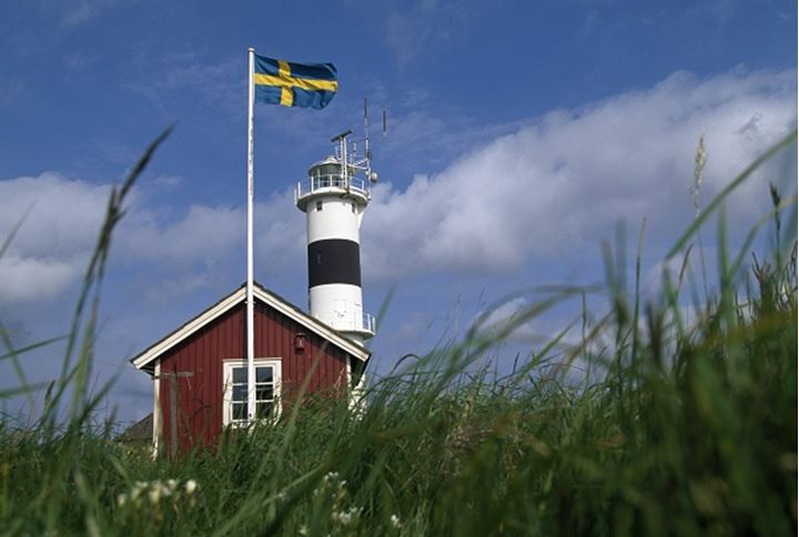 Red house, lighthouse and Swedish flag, Sweden