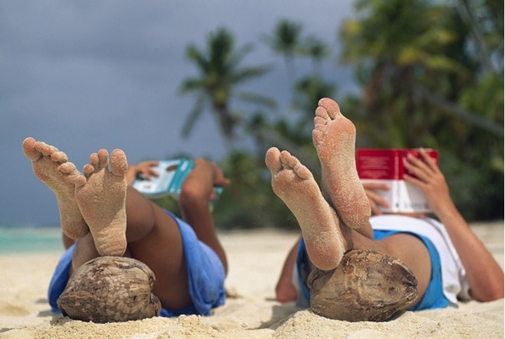 Couple reading books with feet resting on coconuts