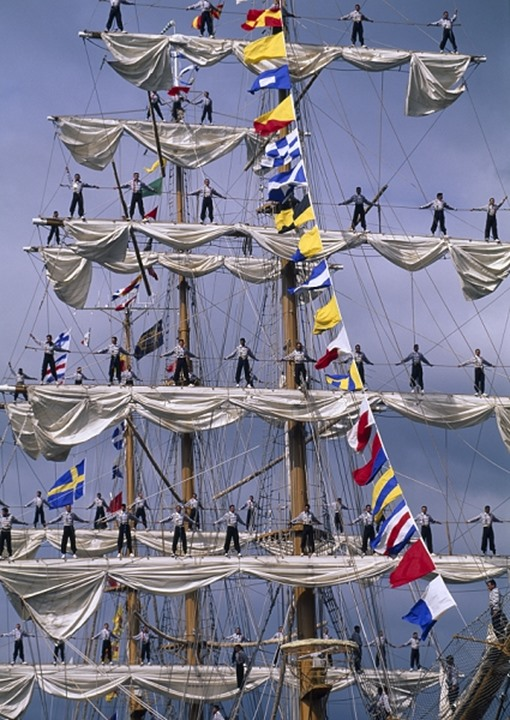 Sailors standing on the crossbars of a triple masted schooner