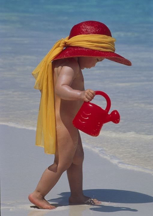A little girl with a sun hat playing with a watering can on the beach