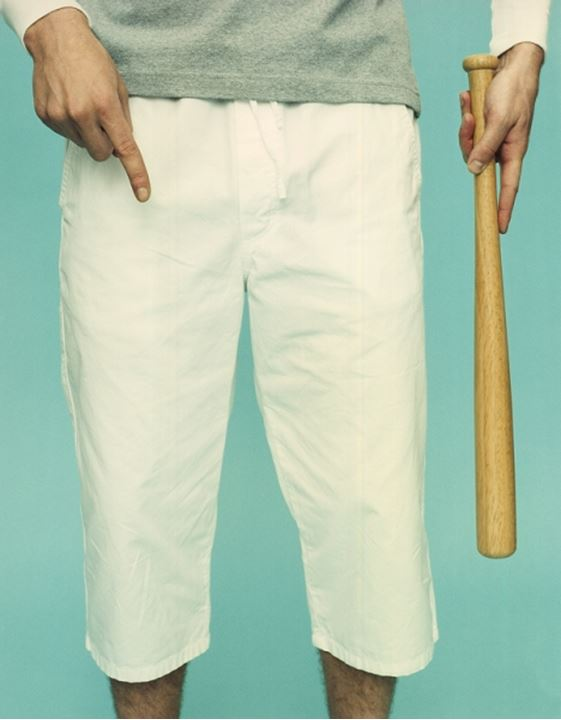 Low section view of a person holding a baseball bat and pointing downwards