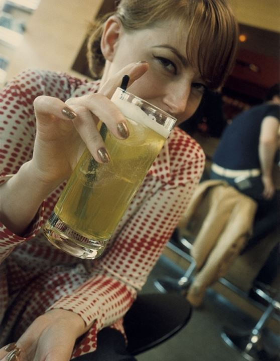 Portrait of a young woman holding a glass of beer