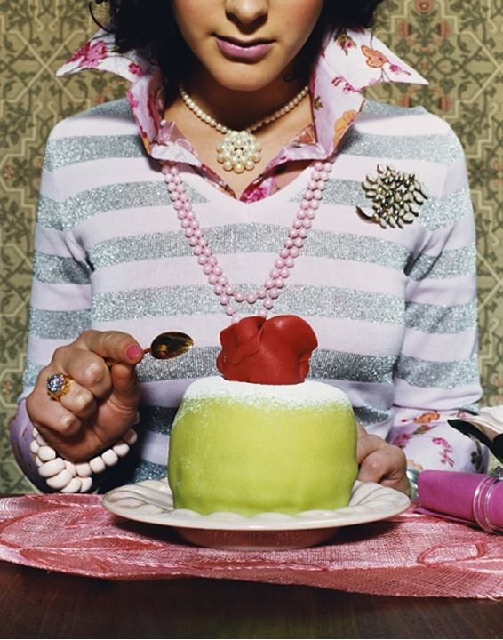 A girl sitting an eating a cake