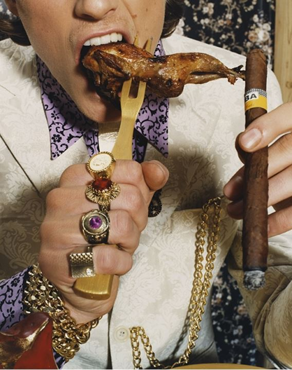 A person dressed as a king eating a chickenwing