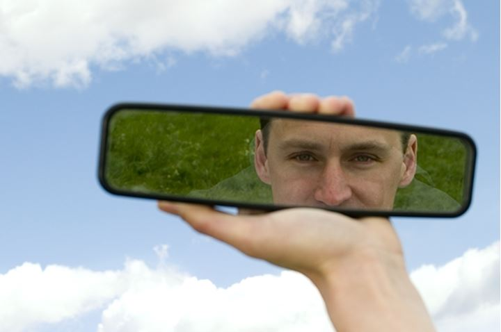 A man looking at himself in a rear view mirror