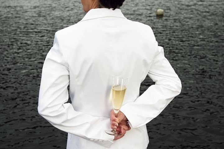 A woman holding a glass of champagne behind her back