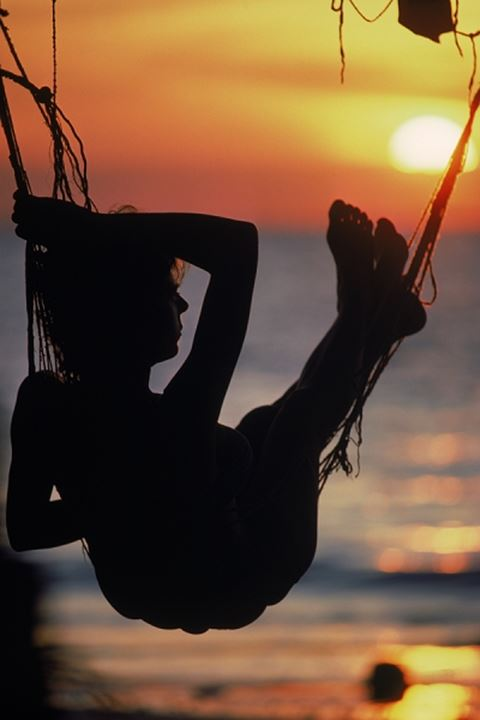 Woman in hammock silhouetted at sunset