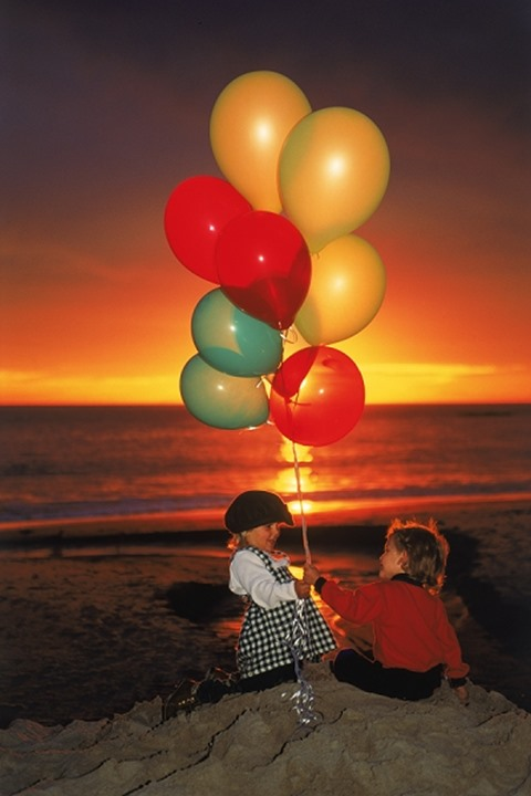 Two chirldren on beach with balloons at sunset