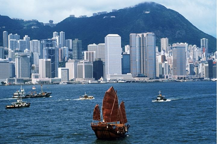 Old junk with red sails passing Hong Kong skyline